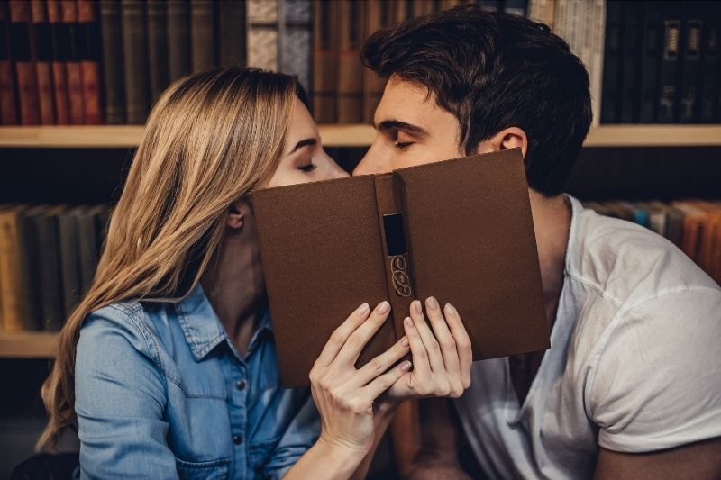 students kissing inside the library covering face with a book