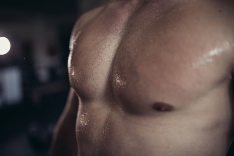 sweaty man's torso standing in the gym in cropped image
