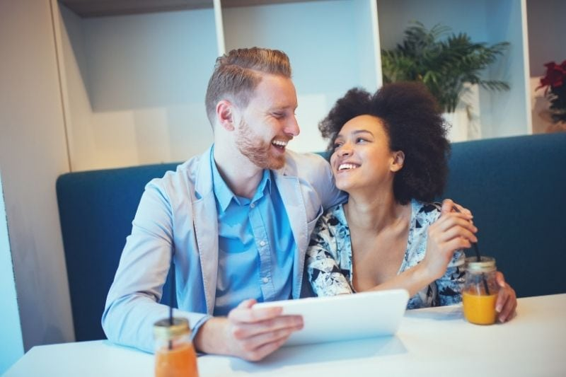 sweet multiracial couple of a red head man and an afro american woman dating inside a cafe