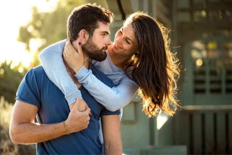 sweet woman hugging a handsome man outdoors