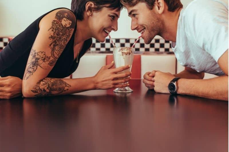 tattoed woman and non tattoed man enjoying one milkshake together