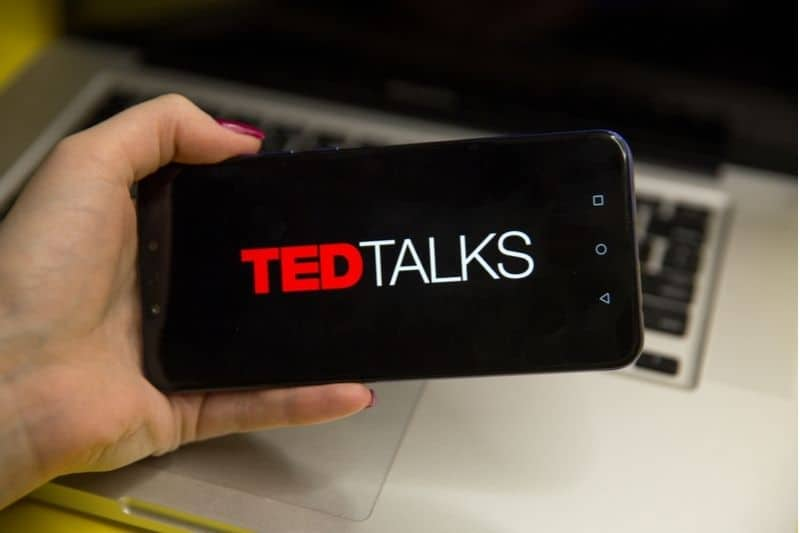 ted talks logo shown on the smartphone held by a woman cropped