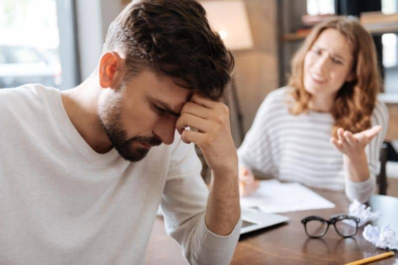thoughtful sad man holding his forehead and a woman nagging