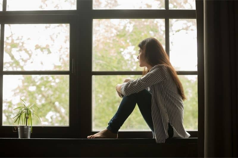 thoughtful woman sitting on the window sill