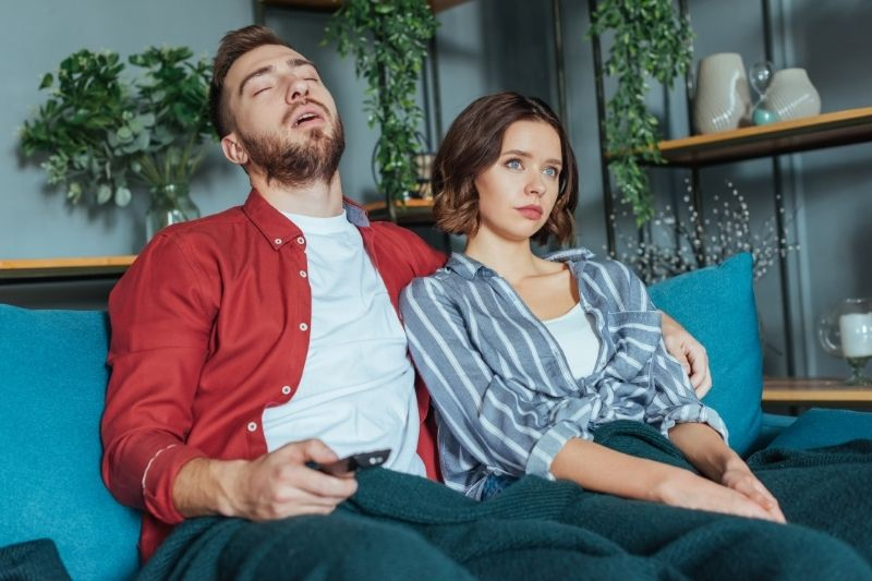 tired man holding a remote control while watching tv with a woman beside him sitting on sofa