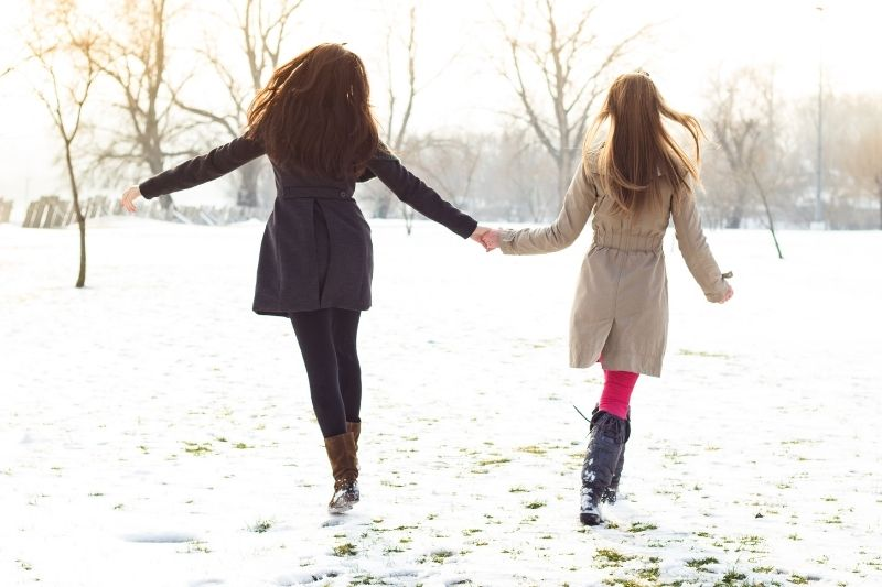 two bestfriends walking in the snow holding hands playfully