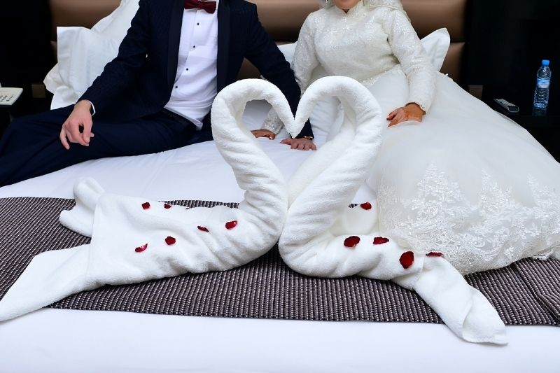 two towels swan shaped in hotel bed with a newly wed couple cropped at the back
