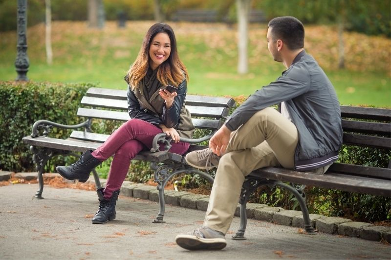 two young people sitting on a separate benches of the park talking and smiling