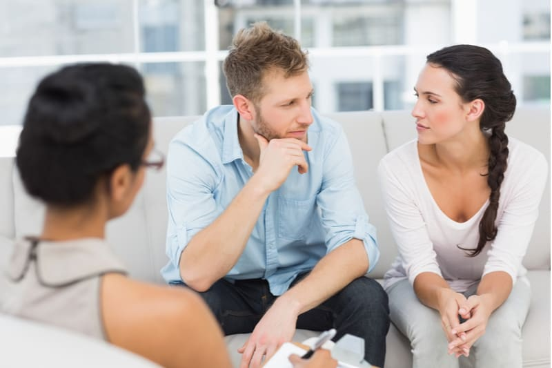 unhappy couple therapy session with a therapist listening