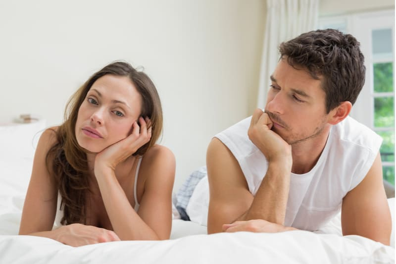 upset woman talking with a man lying down on their bed with white linen