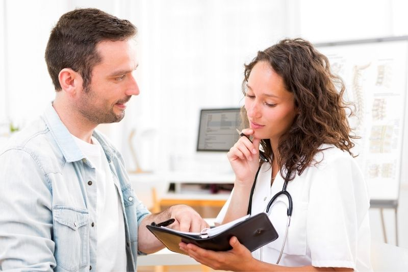 view of a young woman doctor dating a guy while looking at her planner inside the clinic