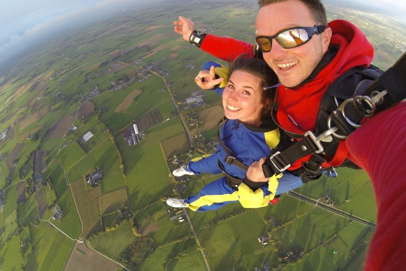 woman in blue jacket and man doing sky diving