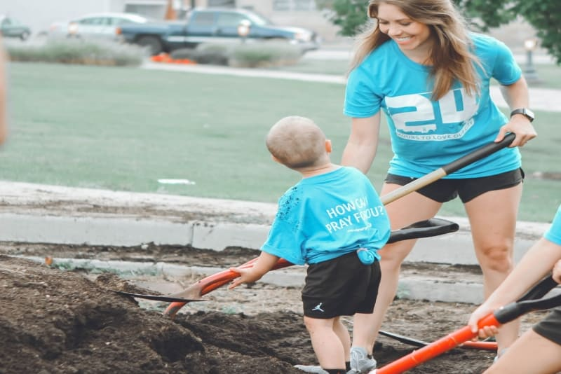 woman and toddler holding brown and black shovels outdoor