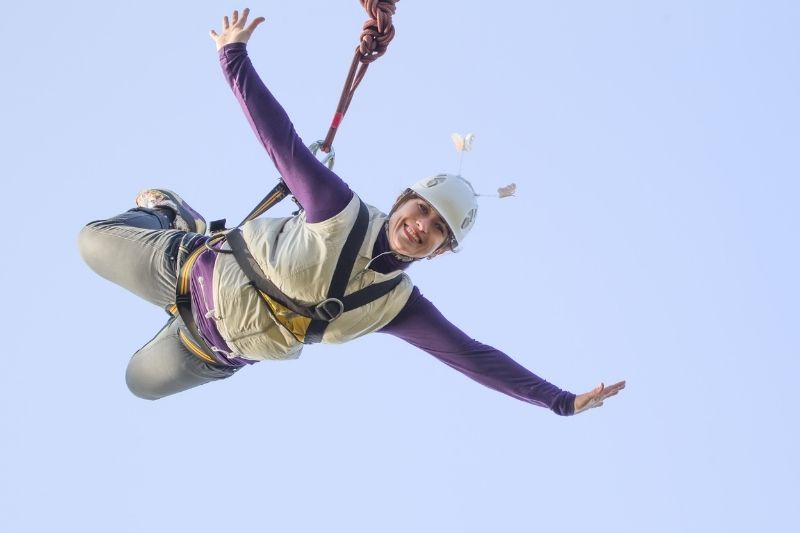 woman bungee jumping smiling against clear blue sky