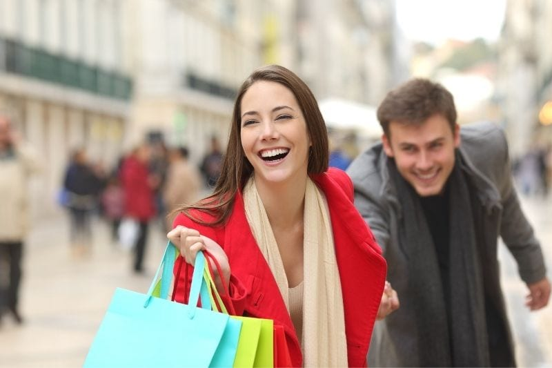 woman dragging the man on shopping while carrying shopping bags