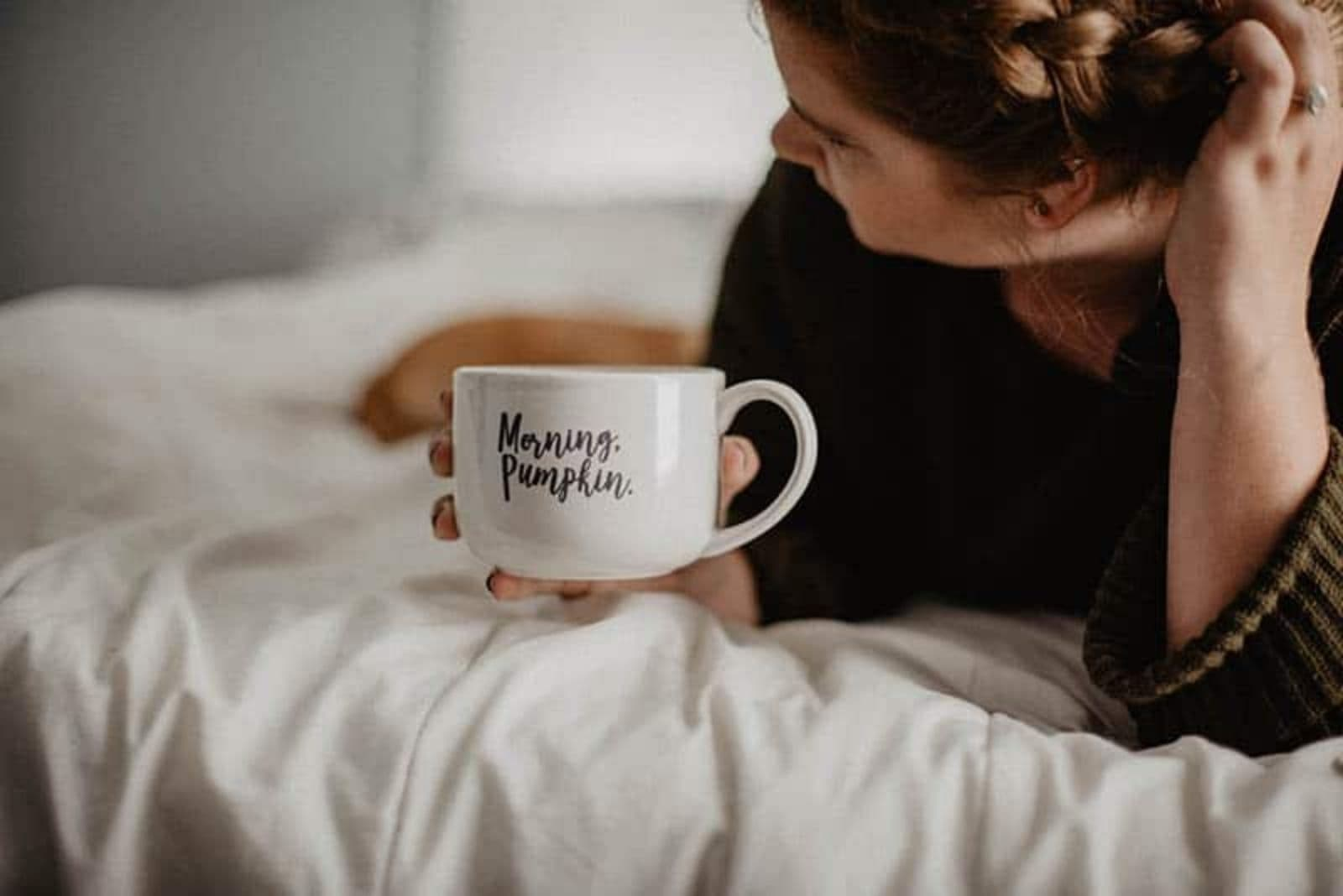 woman drinking her morning coffee in bed