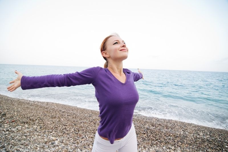 woman enjoying peace and tranquility in the beach raising her arms