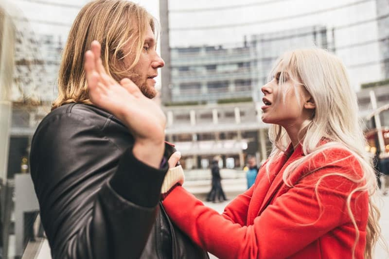woman grasping a man's jacket in the public during a fight