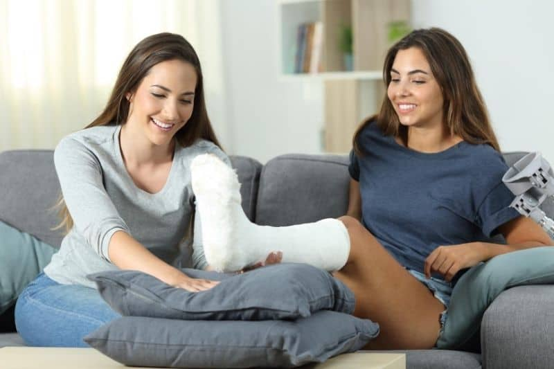 woman helping her disabled friend putting her injured leg on the pillows on the table