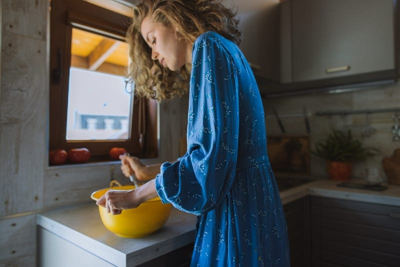 woman holding yellow bowl while standing in kitchen