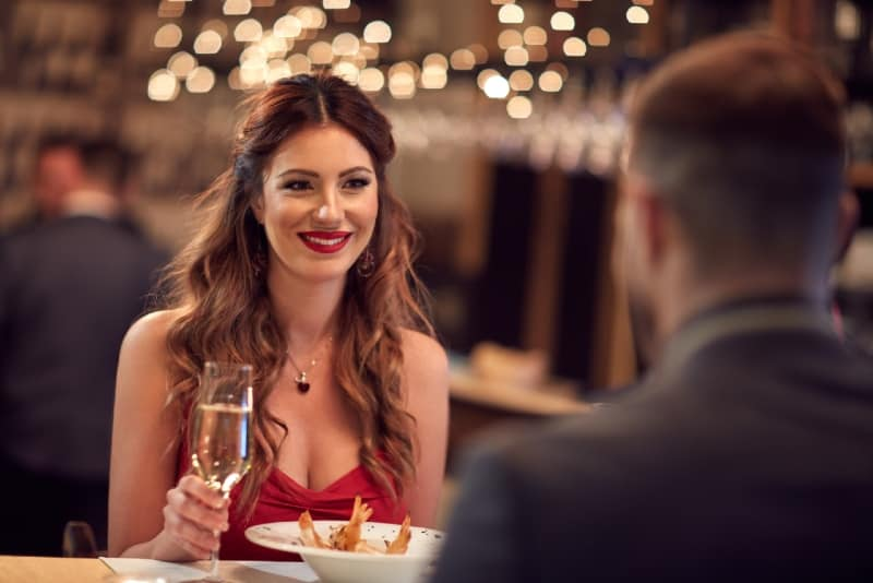 happy woman in red dress holding glass of wine