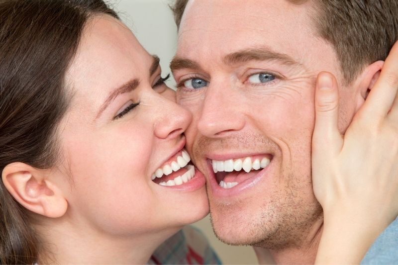 woman holding man's face close to hers laughing focus on the faces