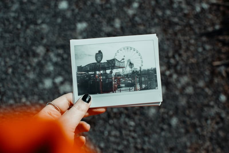 woman holding polaroid picture of an amusing park cropped