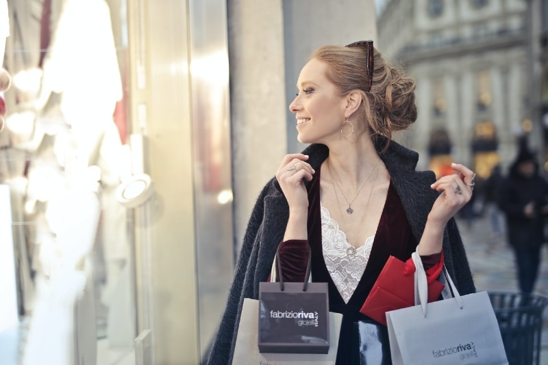 woman in black blazer holding shopping bags