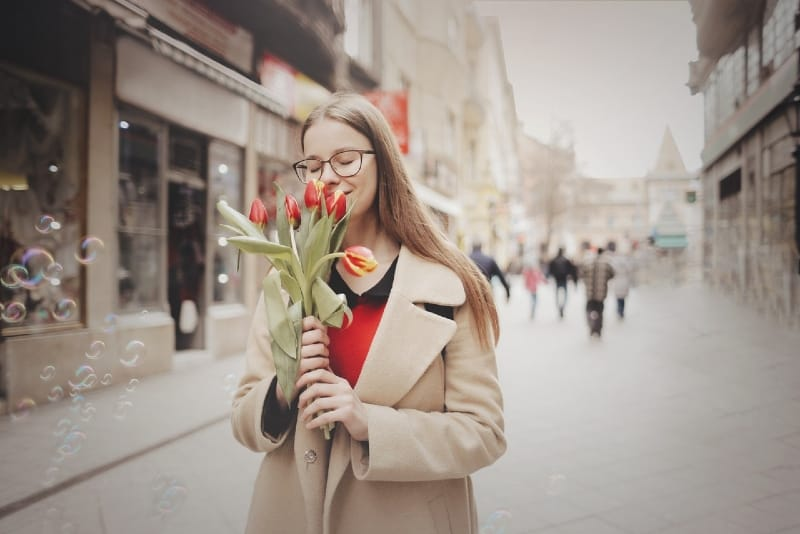 woman in beige coat holding tulips