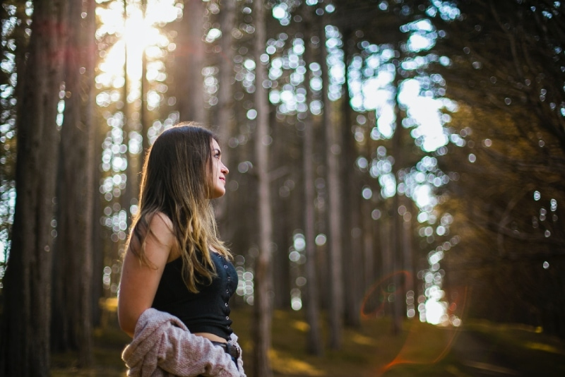 woman in black top standing in forest
