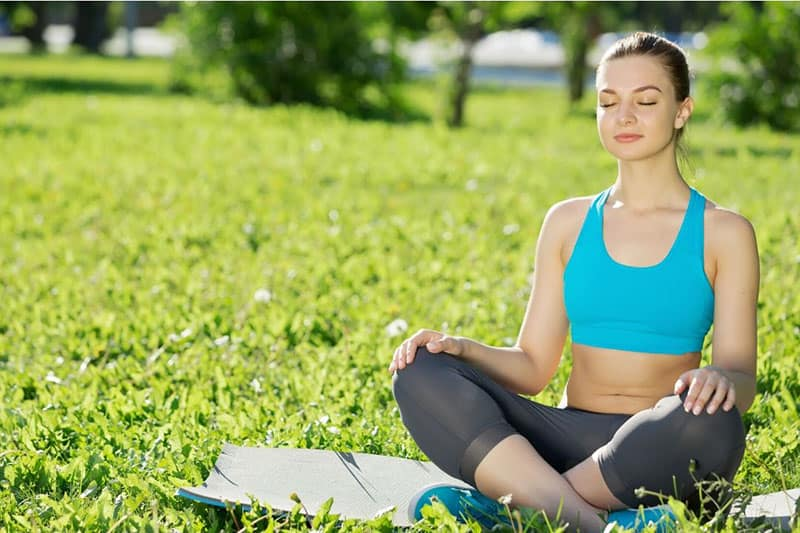 woman in yoga pose meditating outdoors with a mat on top of the green grasses