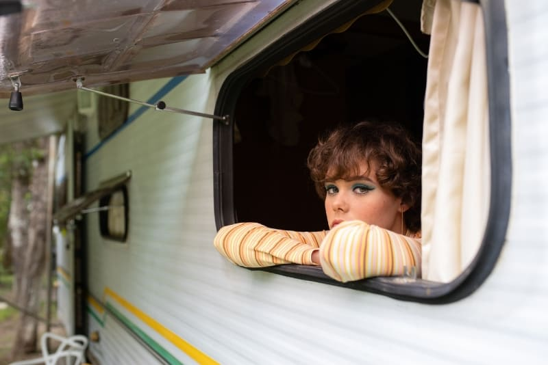 woman in yellow striped top leaning on window of camper