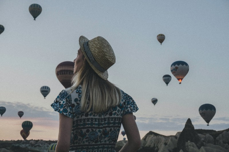blonde woman with hat looking at air balloons