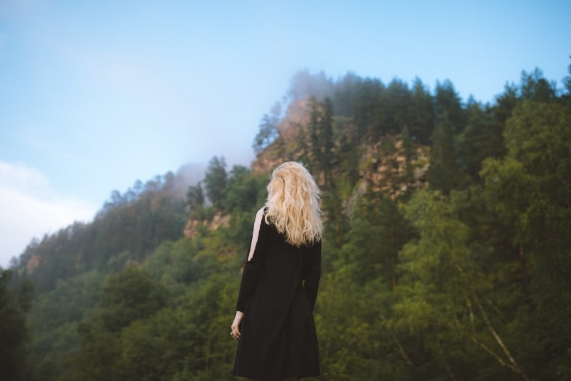 blonde woman in black dress looking at mountain