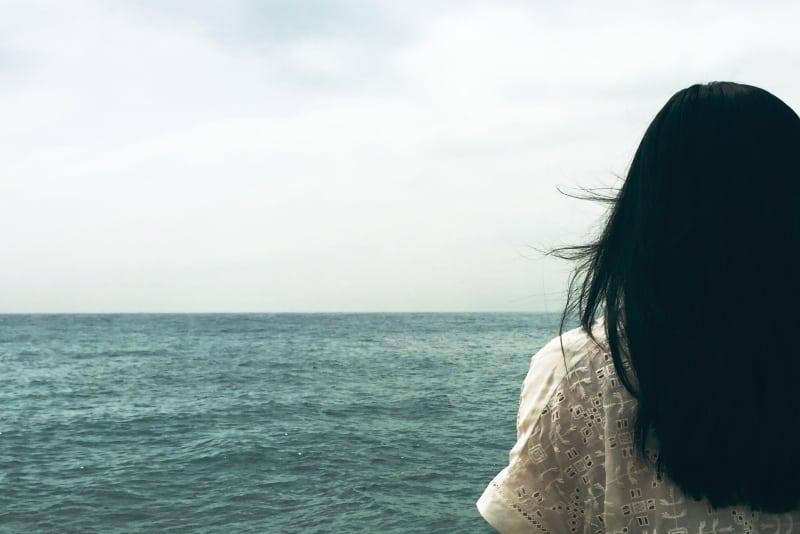 woman in white top looking at ocean