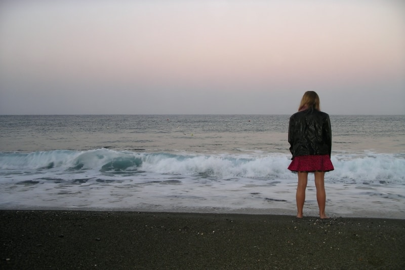 woman standing on seashore looking at sea