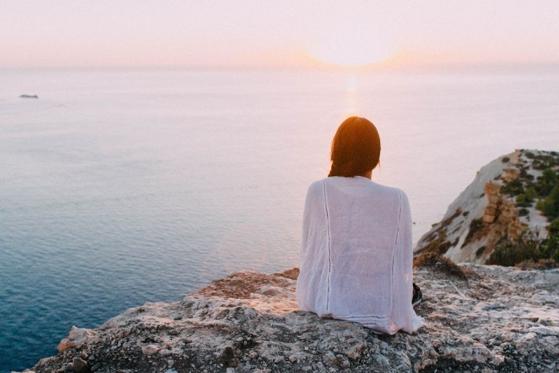 woman looking at sunset while sitting on rock