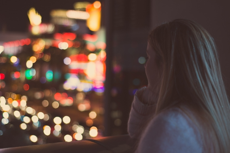 blonde woman looking outside at night