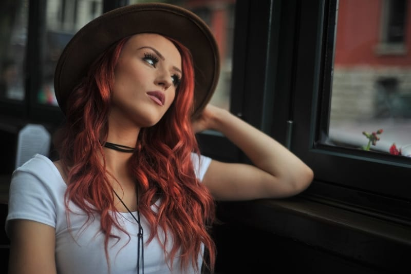 red haired woman with hat looking through window