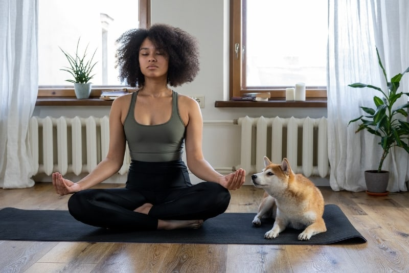 woman meditating while sitting near dog