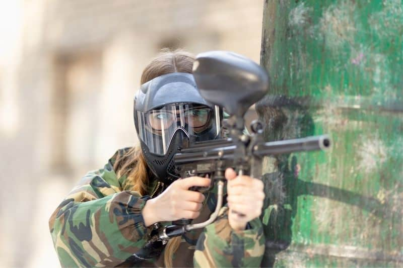 woman playing paintball with complete geared overall leaning and hiding ready to shoot
