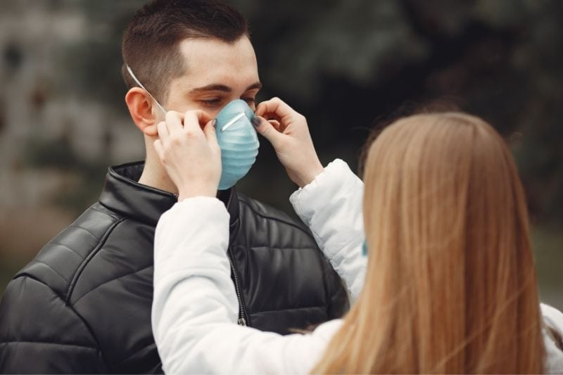 woman putting facemask on a man outdoors