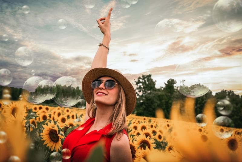 happy woman surrounded with sunflowers raising hand