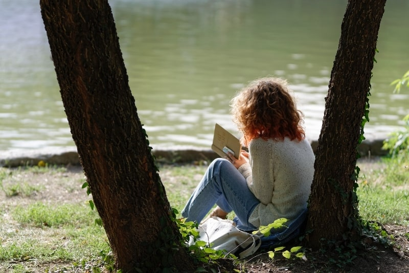 woman reading a book while sitting near tree