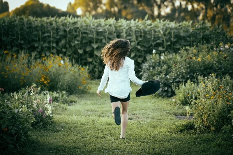 woman in white shirt running on green grass