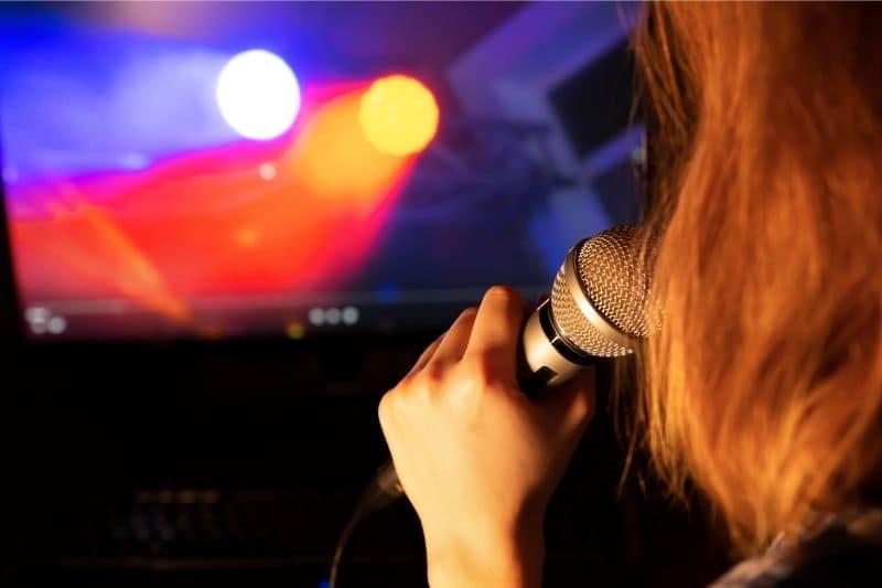 woman singing karaoke alone during a self quarantine