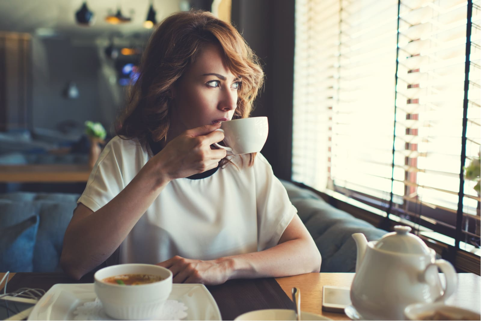 woman sitting in cafe drinking coffee