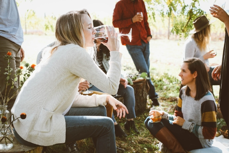 woman sitting near people while drinking wine