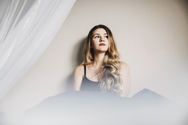 blonde woman in black top sitting near wall