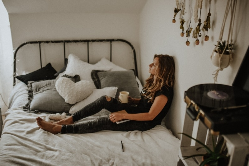 woman holding white mug while sitting on bed